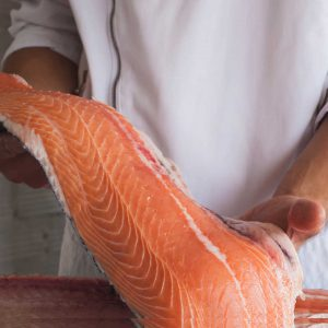 Chef holding a raw salmon fillet