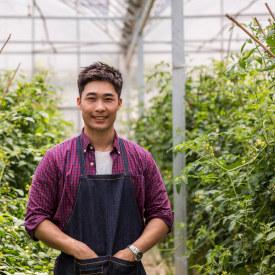 young male farmer checking plants in organic farm