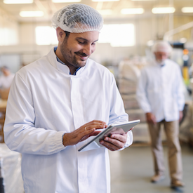 Man in hairnet and white coat with a tablet in a food processing plant