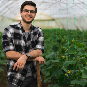 Young man in a black plaid shirt leaning on a stick in a greenhouse facility with crops