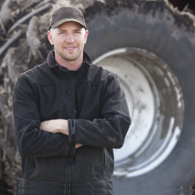 Young man in black hat and black jacket in front of large scale agriculture equipment tires