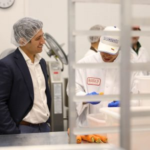Image of man in suit with hair net speaking to a man in a hat and white coat in a food processing facility to make soup